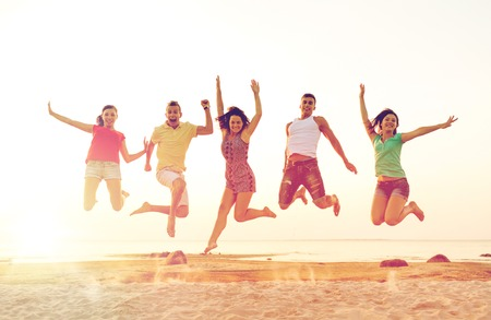 smiling friends dancing and jumping on beach