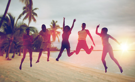 happy friends dancing and jumping on beach photo