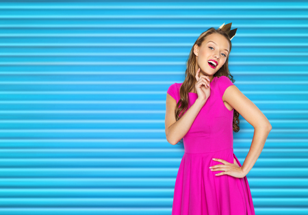 happy young woman or teen girl in pink dress