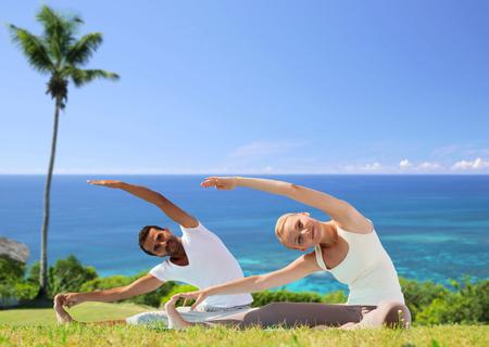 happy couple making yoga exercises outdoors Stock Photo