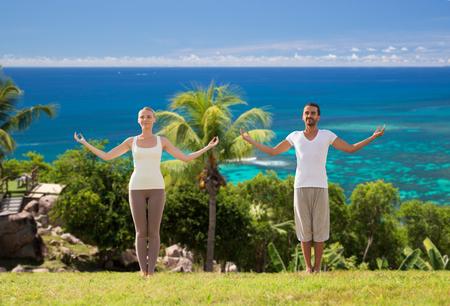 happy couple making yoga exercises on beach photo
