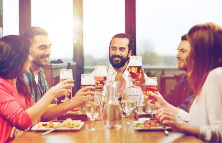 Amici, cenare e bere birra al ristorante Archivio Fotografico - 83741823