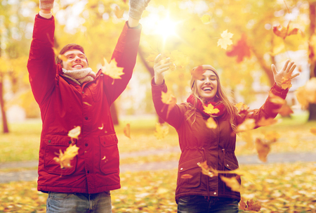 happy young couple throwing autumn leaves in park Stock Photo