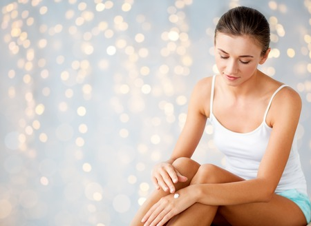 beautiful woman applying hand cream at home