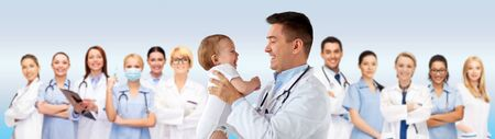 happy doctor or pediatrician with baby over blue photo