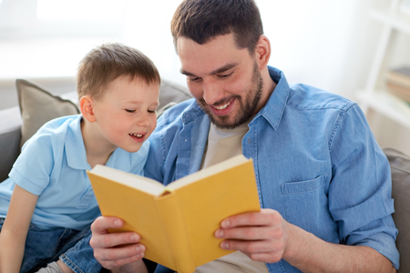 happy father and son reading book sofa at home