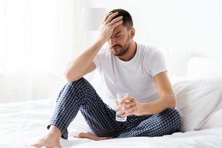 Homme au lit avec un verre d'eau à la maison Banque d'images - 83703477