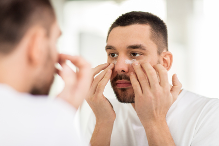 metrosexual: young man applying cream to face at bathroom