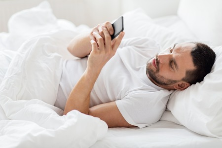 young man with smartphone in bed in morning Stock Photo