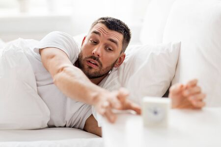 awaking: young man in bed reaching for alarm clock
