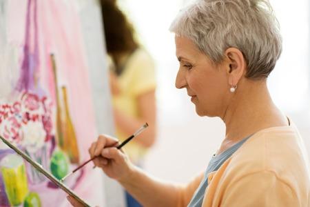 年配の女性アーティストの美術学校で絵画