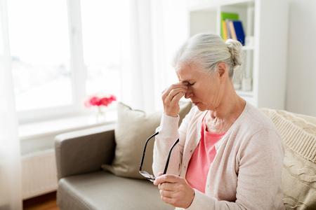 Ältere Frau mit Brille , die Kopfschmerzen zu Hause haben Standard-Bild