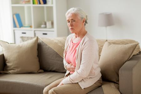 senior vrouw die thuis lijdt aan buikpijn