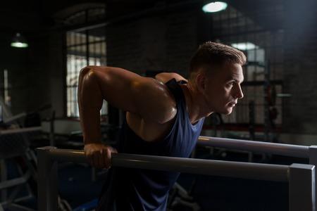 Man faisant triceps dip sur les barres parallèles dans le gymnase Banque d'images - 83742012