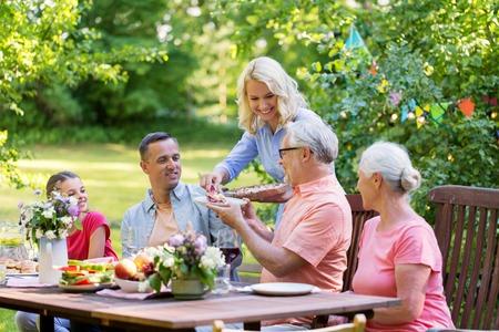 happy family having dinner or summer garden party Zdjęcie Seryjne