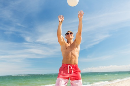 young man with ball playing volleyball on beach