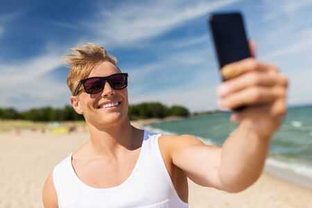 man with smartphone taking selfie on summer beach Фото со стока