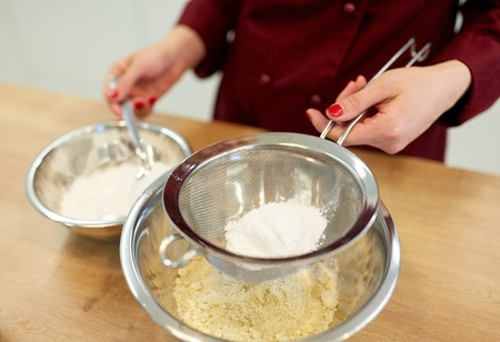 chef with flour in bowl making batter or dough 版權商用圖片