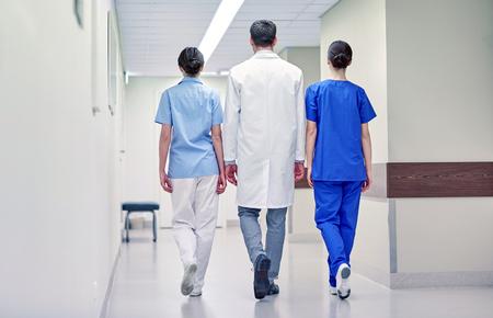 group of medics or doctors walking along hospital