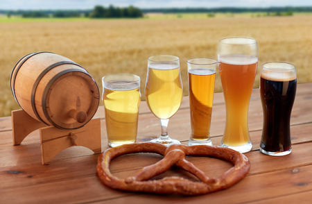 beer glasses, barrel and pretzel over cereal field