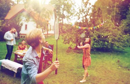 Amis heureux de jouer au badminton au jardin d'été Banque d'images - 83786116
