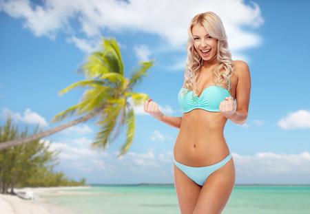 happy woman in bikini doing fist pump on beach