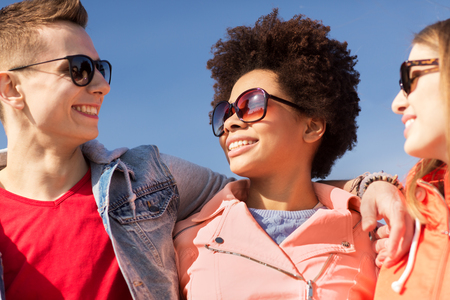 happy teenage friends in shades talking on street photo