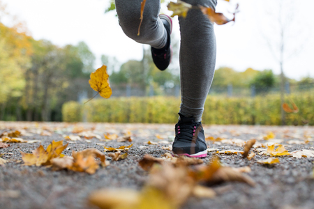 close up of young woman running in autumn park Stok Fotoğraf