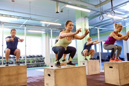 group of people doing box jumps exercise in gym photo