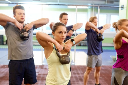 group of people with kettlebells exercising in gym photo