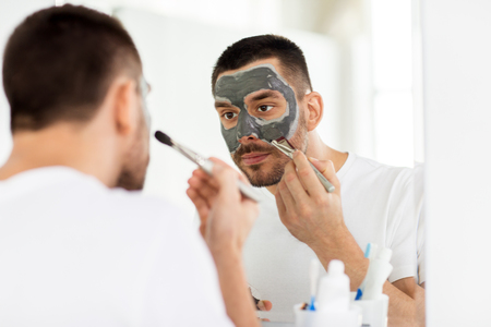 young man applying clay mask to face at bathroom