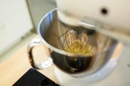 electric mixer whipping egg whites at kitchen
