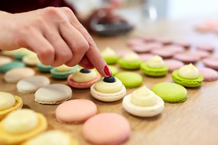 chef-kok versieren macarons schelpen in patisserie