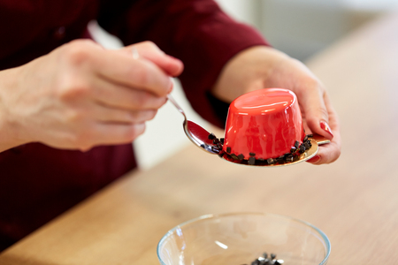 mirror: chef decorating mirror glaze cakes at pastry shop Stock Photo