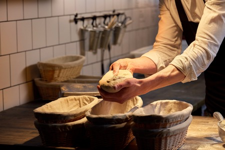 baker with rising in baskets at bakery