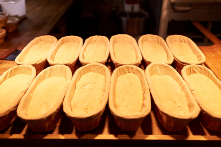 yeast bread in baskets at bakery kitchen Banco de Imagens