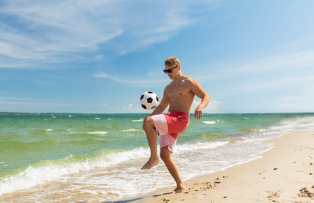 young man with ball playing soccer on beach