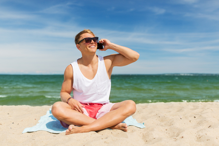 smiling man calling on smartphone on summer beach