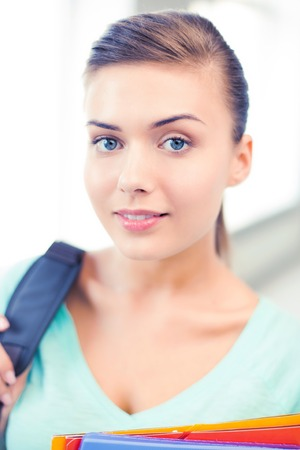 student girl with school bag and color folders photo