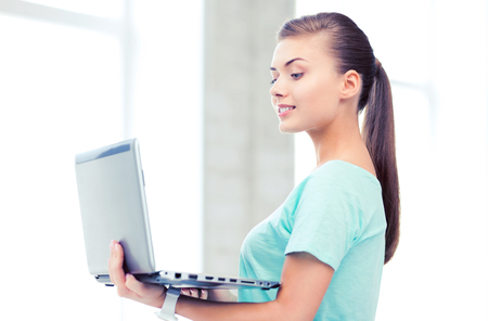 smiling student girl with laptop at school photo