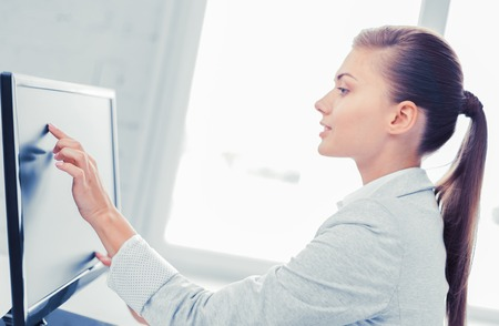 smiling businesswoman with touchscreen in office photo