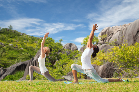 couple making yoga in low lunge pose outdoors photo