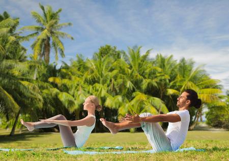 couple making yoga half-boat pose outdoors