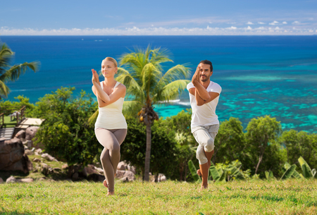 smiling couple making yoga exercises outdoors photo