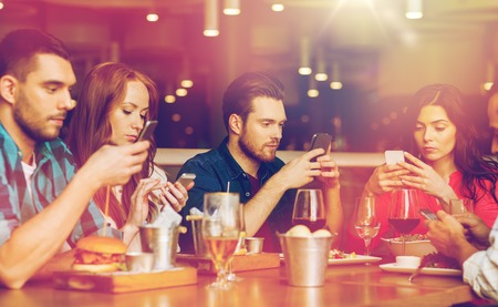friends with smartphones dining at restaurant photo