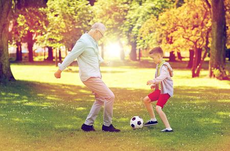 old man and boy playing football at summer park Stock Photo - 83918281