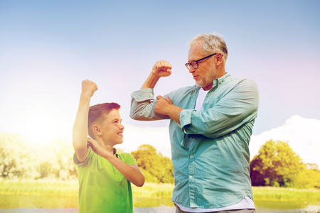 happy grandfather and grandson showing muscles