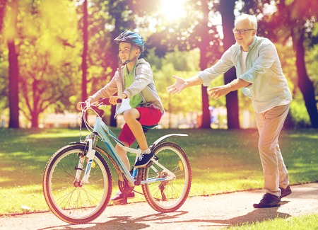 grandfather and boy with bicycle at summer park Stock Photo