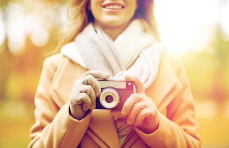 秋の公園でカメラを持つ女性のクローズ アップ