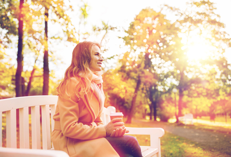happy young woman drinking coffee in autumn park photo